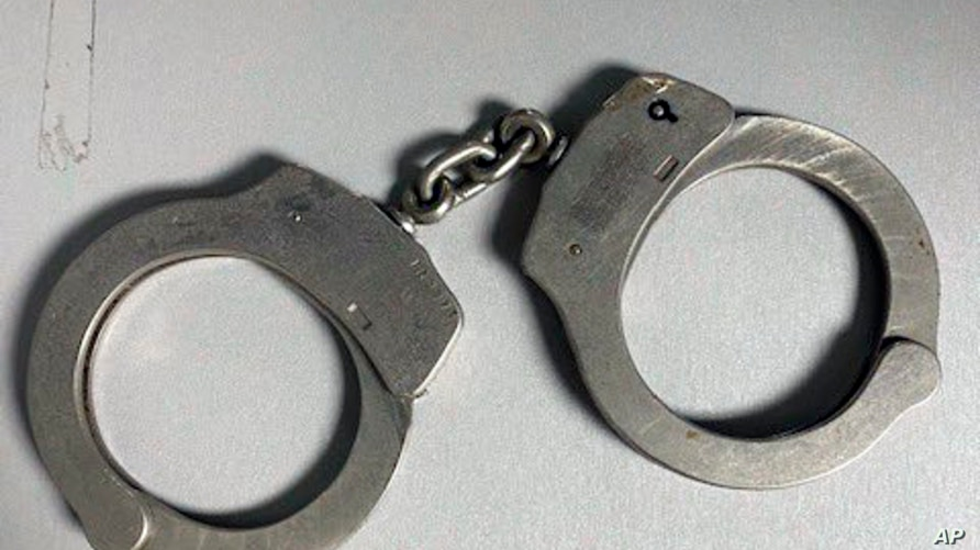FILE - A pair of handcuffs and a key.