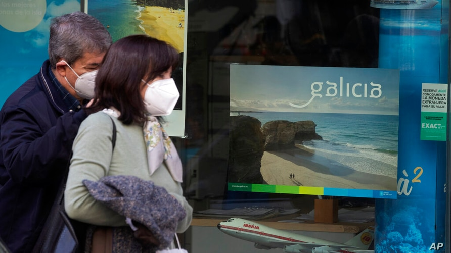 A couple wearing face masks to protect against the spread of coronavirus walk past a closed travel agents in Madrid, Spain,…