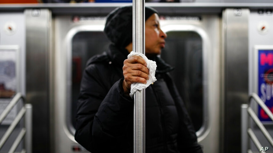 FILE - In this March 19, 2020, file photo, a subway passenger uses a tissue to protect her hand while holding onto a pole as…