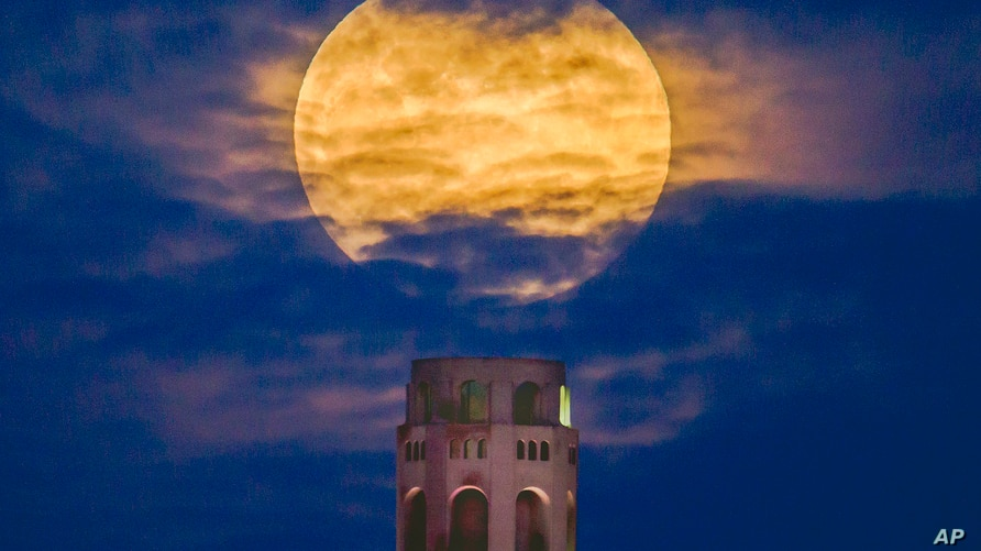 A pink supermoon rises in the night sky over Coit Tower in San Francisco on Monday, April 26, 2021. The full moon in April is…