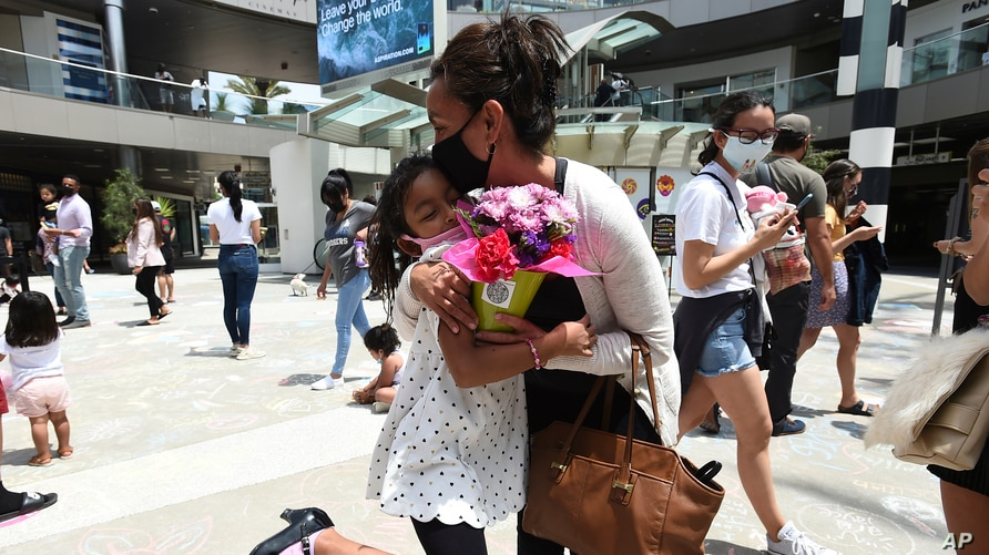 A girl shares a Teleflora bouquet with her mother as part of Teleflora's Mother's Day.