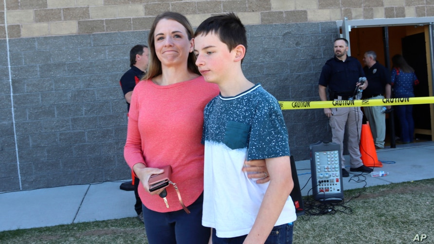 Alicia Willis walks away with her son at a high school where people were evacuated after a shooting at the nearby Rigby Middle…