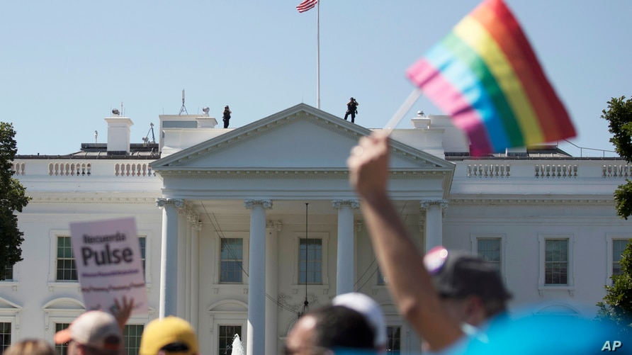 FILE - In this June 11, 2017 photo, Equality March for Unity and Pride participants march past the White House