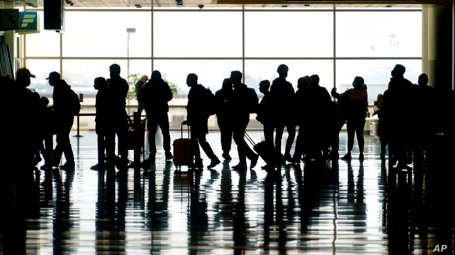 FILE - In this Wednesday, March 17, 2021 file photo, travelers walk through the Salt Lake City International Airport in Salt…