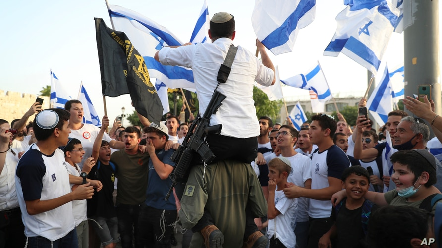 Israelis nationalists wave national flags during a Jerusalem Day march, in Jerusalem, Monday, May 10, 2021.