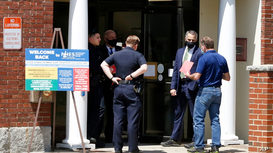 A job seekers receives a timed entry card as he enters the New Hampshire Works employment security job center, Monday, May 10,…