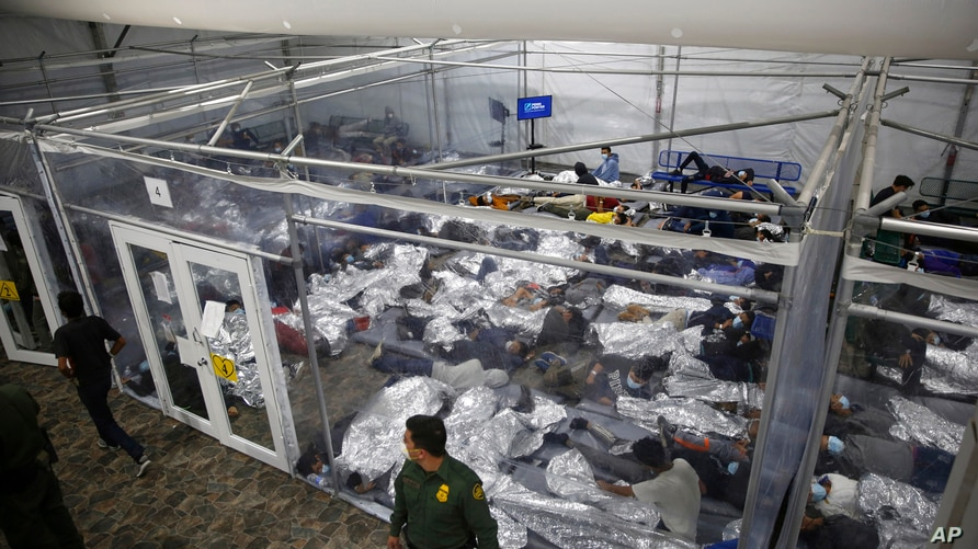 Young minors lie inside a pod at the Donna Department of Homeland Security holding facility, the main detention center for unaccompanied children in the Rio Grande Valley, in Donna, Texas, March 30, 2021.