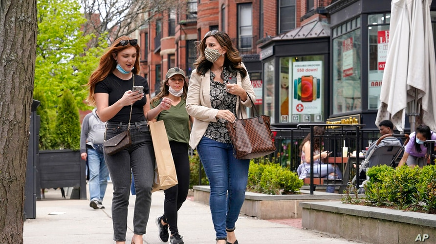 FILE - In this May 2, 2021, file photo, pedestrians walk along Boston's fashionable Newbury Street. COVID-19 deaths in the U.S…