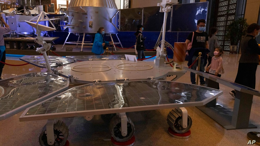 Visitors to an exhibition on China's space program look at a life size model of the Chinese Mars rover Zhurong, named after the…
