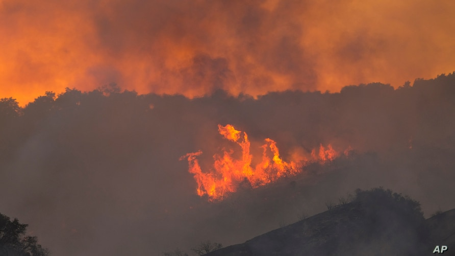 Flames from a brush fire in the Pacific Palisades area of Los Angeles, May 15, 2021.