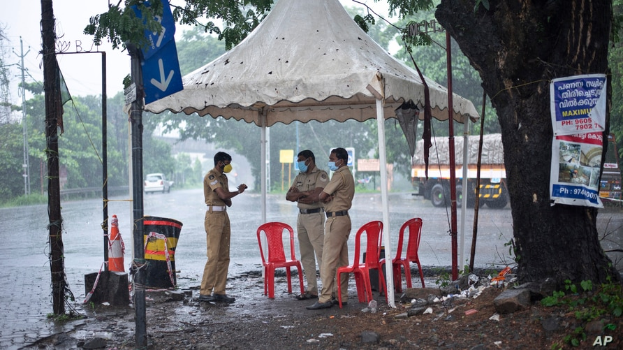 Policemen enforcing a lockdown to curb the spread of coronavirus stand beneath a rain shelter in Kochi, Kerala state, India, Sunday, May 16, 2021.