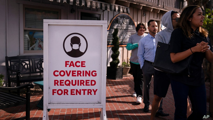 People walk past a sign requesting customers to wear masks in Laguna Beach, Calif., Monday, May 17, 2021. California won't lift…