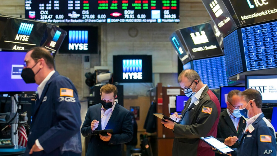 In this photo provided by the New York Stock Exchange, traders work on the floor of the NYSE, Tuesday, May 18, 2021. Stocks…