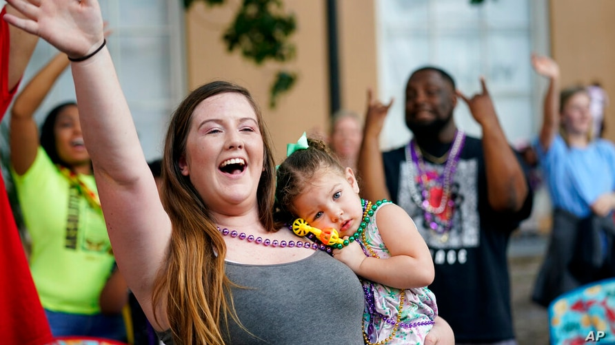 """Hayley Bosarge vies for throws as she holds her daughter Ellie Bosarge, 2, during a parade dubbed """"Tardy Gras,"""" to compensate…"""