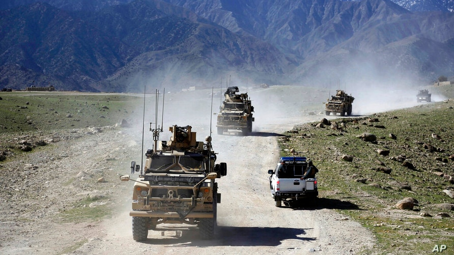 FILE - In this April 2014 file photo, U.S. forces and Afghan commando patrol Pandola village near the site of a U.S. bombing in…