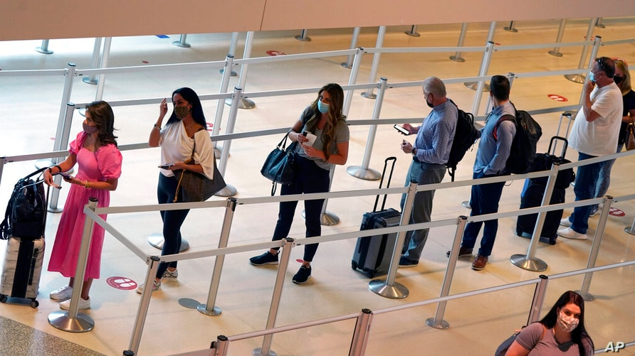 Travelers wait to clear the security check point at Love Field airport Friday, May 28, 2021, in Dallas. (AP Photo/LM Otero)