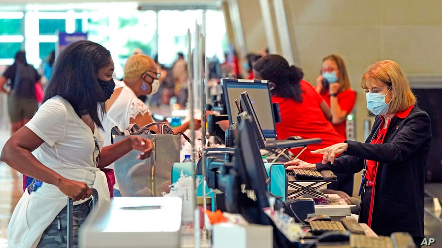 Travelers check in at Love Field airport Friday, May 28, 2021, in Dallas. (AP Photo/LM Otero)