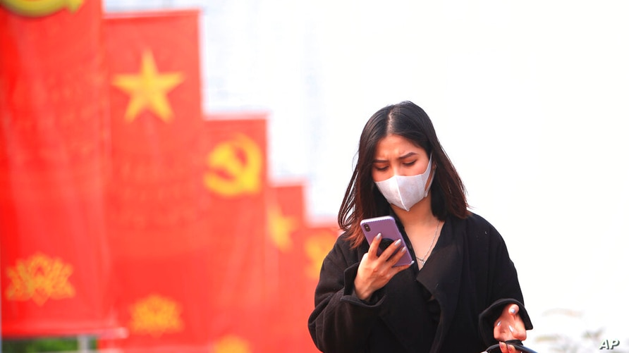 FILE - In this Jan. 23, 2021 file photo, a woman wearing face mask looks at her phone in Hanoi, Vietnam.  Vietnam says it has…