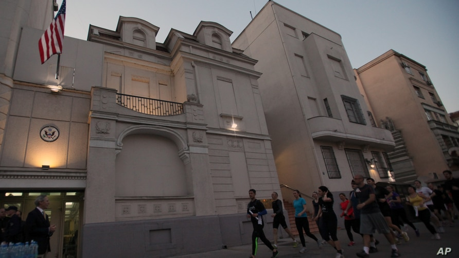 Runners arrive to the US embassy in an organized memorial run to show solidarity with victims of the Boston Marathon bombing,…