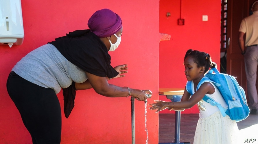 FILE - A staff member, wearing a protective facemask, helps a student to wash her hands at Malamani Primary School, in Chirongui, on the French Indian Ocean island of Mayotte, May 27, 2020.