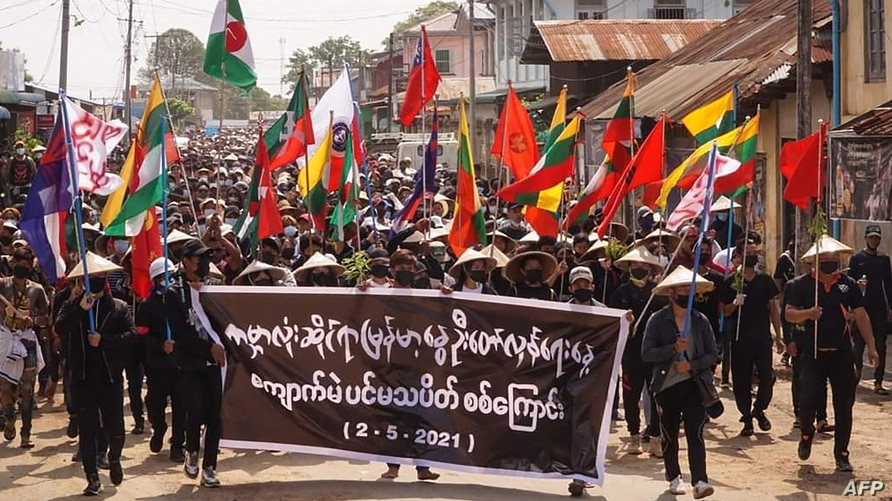 """Protesters holding a banner and flags take part in a demonstration against the military coup on """"Global Myanmar Spring Revolution Day"""" in Kyaukme in Myanmar's Shan State, May 2, 2021. (Credit: Shwe Phee Myay News Agency)"""