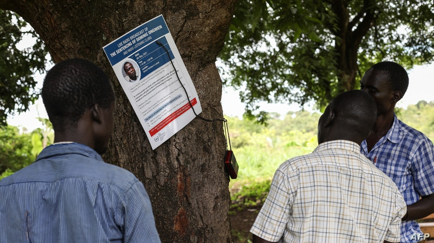 Residents of Lukodi village, where dozens were killed in 2004 by the Lord's Resistance Army, react as they listen to the International Criminal Court's sentence of Dominic Ongwen, on radio in Lukodi, Uganda, May 6, 2021.