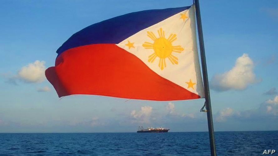FILE - This handout photo taken April 14, 2021, and received from the Philippine Coast Guard April 15, 2021, a Philippine flag is displayed aboard a coast guard vessel as it patrols in waters off the Spratly Islands.