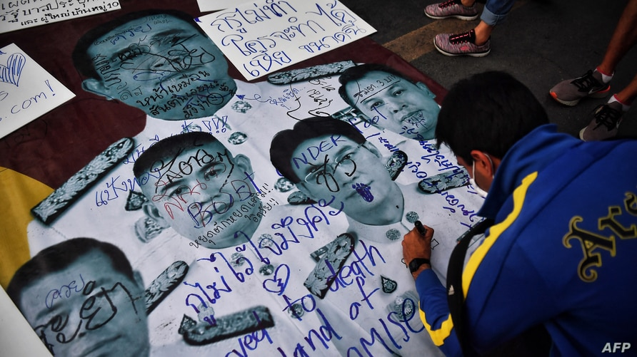 FILE - A protester writes pro-democracy messages on images of Thailand's Prime Minister Prayut Chan-ocha and top Thai generals during an anti-government rally in Bangkok, Feb. 20, 2021.