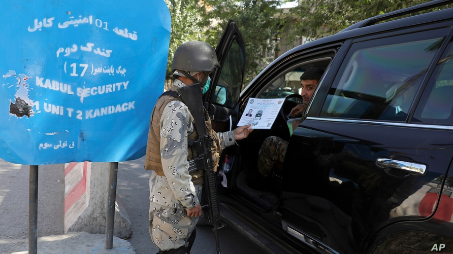 Afghan security personnel search a car at a checkpoint around the Green Zone, which houses embassies, in Kabul, May 25, 2021.