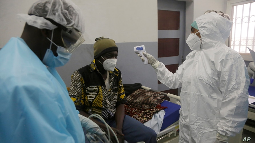 A health worker takes temperature of a COVID-19 patient at the Farcha provincial hospital in N'Djamena, Chad, April 30, 2021.