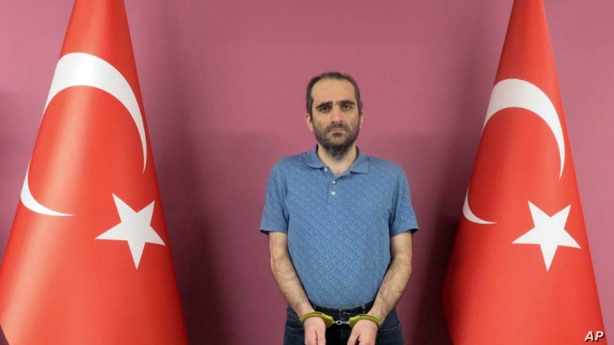 Selahaddin Gulen, a nephew of U.S.-based Muslim cleric Fethullah Gulen, stands between Turkish flags in this photo provided by the Turkish intelligence service, in Ankara, Turkey, May 31, 2021.