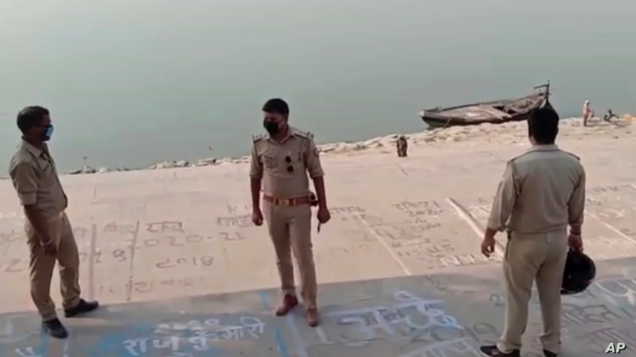 This frame grab from video provided by KK Productions shows police officials standing on the bank of a river where several bodies were found floating, in Ghazipur district, Uttar Pradesh state, India, May 11, 2021.