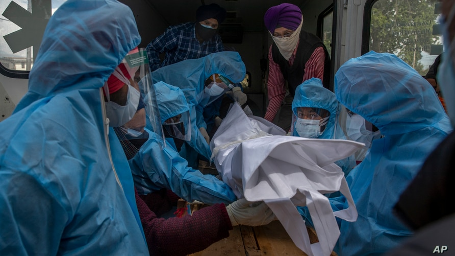 Relatives and volunteers in protective suits take out the body of a COVID-19 victim from an ambulance for cremation at a crematorium in Srinagar, Indian-controlled Kashmir, May 25, 2021.
