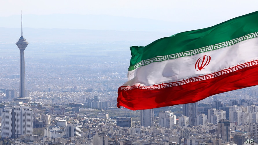 FILE - Iran's national flag flutters in the wind as the Milad telecommunications tower and buildings are seen in the background, Tehran, Iran, March 31, 2020.