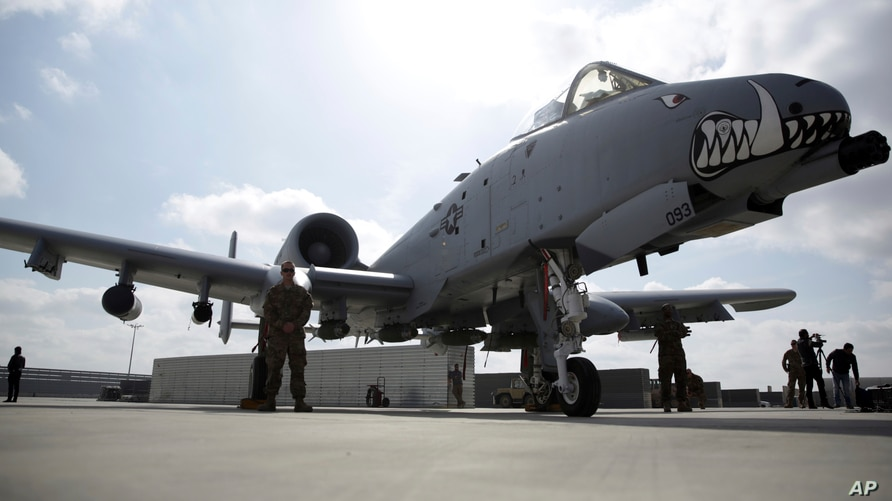FILE - U.S. military personnel stand beside an A-10C fighter at Kandahar Airfield, Afghanistan, Jan. 23, 2018.