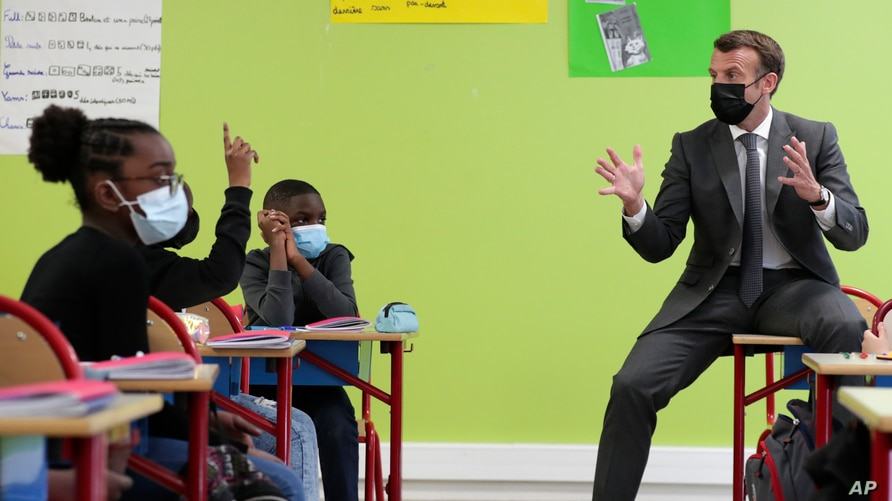FILE - French President Emmanuel Macron talks with students during a visit in a school in Melun, south of Paris, April 26, 2021. The country's Ministry of Education this week took steps to make French more inclusive by feminizing some words.