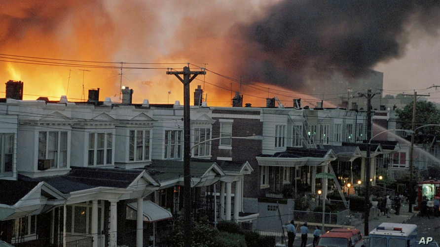 FILE - Row houses burn in a fire in a west Philadelphia, Pennsylvania, neighborhood in May of 1985 after police dropped a bomb on the headquarters of a Black organization in an attempt to arrest members, leading to the burning of dozens of homes.