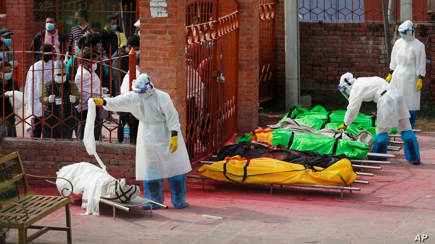 Family members watch as Nepalese army personnel in protective suits prepare the bodies of COVID-19 victims for cremation, near Pashupatinath temple, in Kathmandu, Nepal, May 7, 2021.