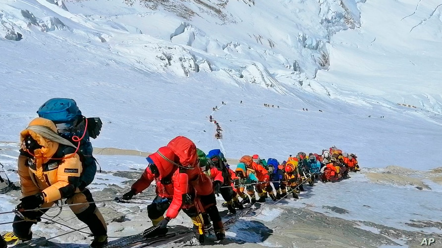 FILE - A long queue of mountain climbers line a path on Mount Everest just below camp four, in Nepal, May 22, 2019.
