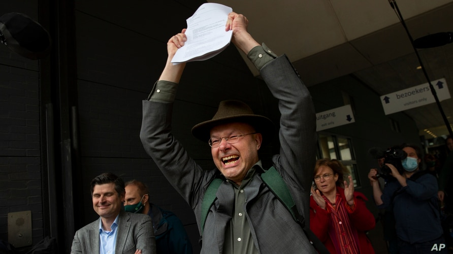 Milieudefensie director Donald Pols, holding a copy of the verdict, celebrates the outcome in the court case of Milieudefensie, the Dutch arm of the Friends of the Earth environmental organization, against Shell in The Hague, Netherlands, May 26, 2021.