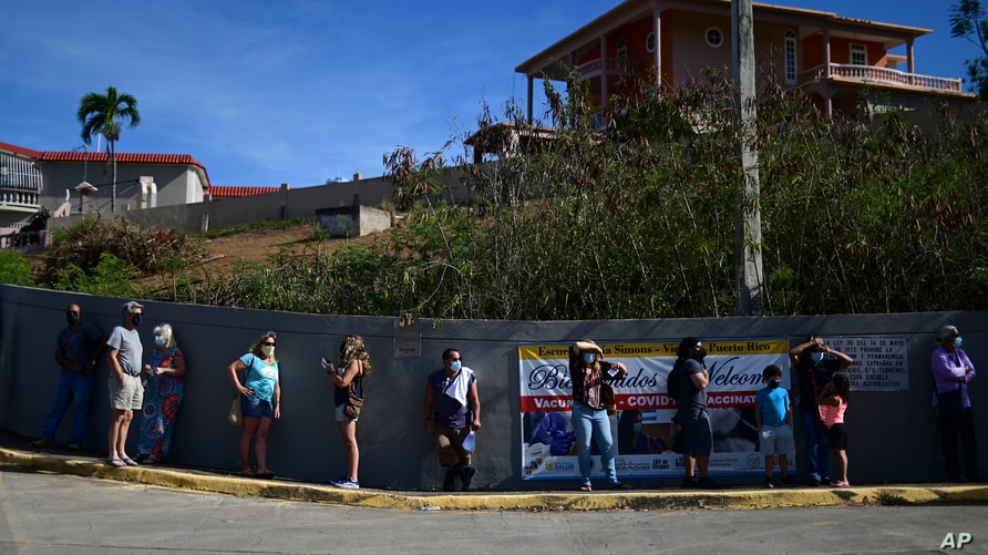FILE - People stand in line outside the Maria Simmons elementary school waiting to be inoculated with the Moderna COVID-19 vaccine as part of a mass vaccination campaign, in Vieques, Puerto Rico, March 10, 2021.
