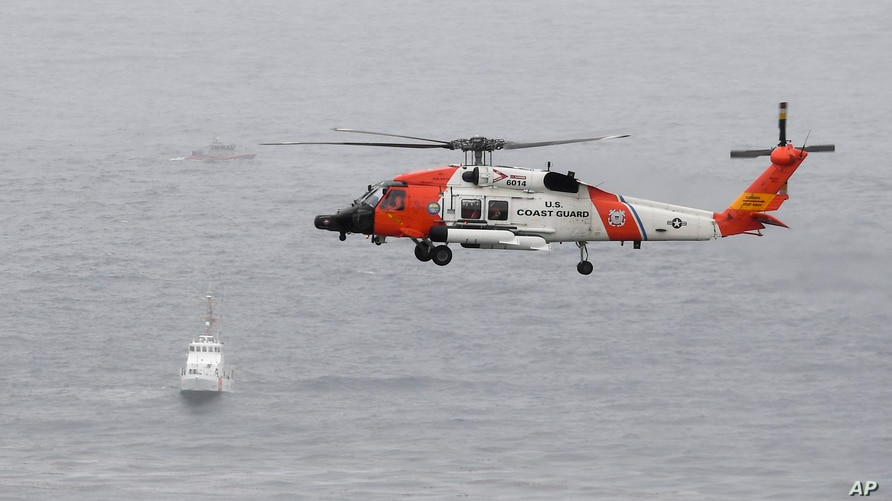 A U.S. Coast Guard helicopter flies over boats searching the area where a boat capsized just off the San Diego coast May 2, 2021, in San Diego, California.