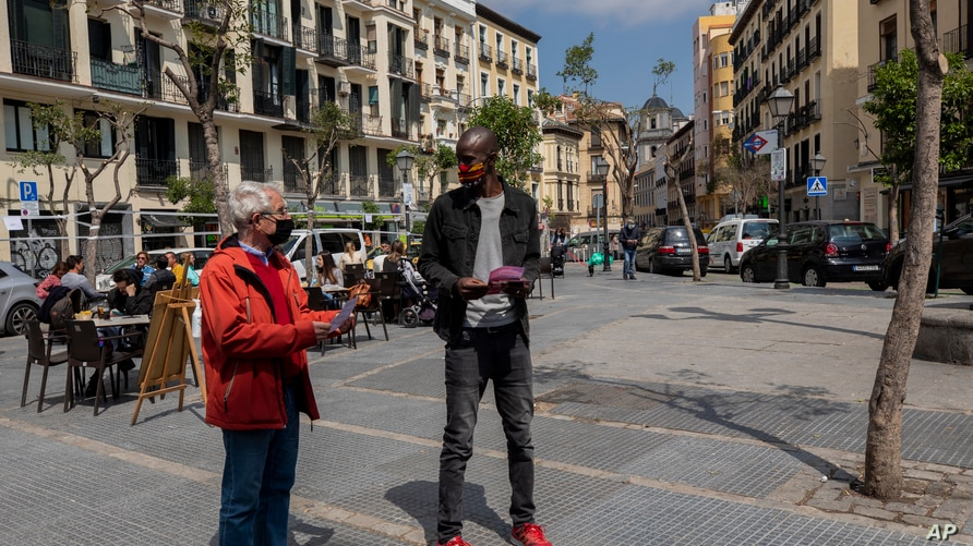 Serigne Mbaye, who is running on a ticket with the anti-austerity United We Can party, talks with a potential voter during an election campaign event in Madrid, Spain, April 16, 2021.