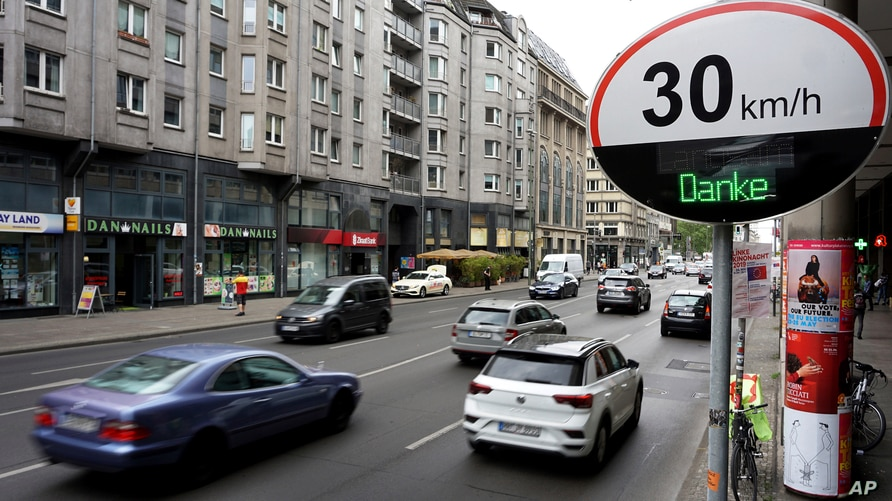 """FILE - Cars pass by a speed limit sign displaying a """"Thank you,"""" on a street in Berlin, Germany, May 20, 2019."""