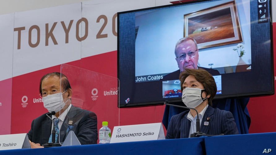 CEO of the Tokyo 2020 Olympics, Toshiro Muto, left, IOC VP John Coates, on screen, and president of the Tokyo 2020 Games, Seiko Hashimoto, are seen at the Tokyo 2020 IOC Coordination Commission press conference, in Tokyo, Japan, May 21, 2021.