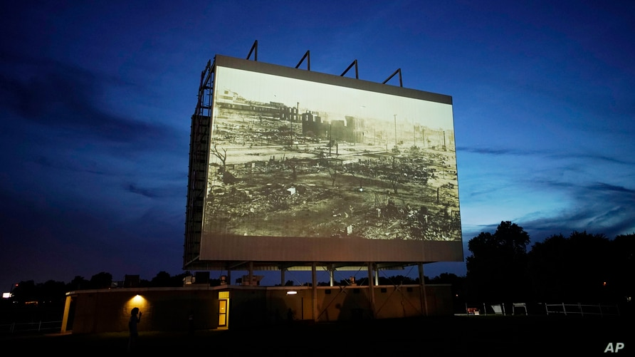 FILE - An image of devastation from the Tulsa Race Massacre is shown on a drive-in movie screen during a screening of documentaries for centennial commemorations of the destruction of a Black neighborhood in Tulsa, Oklahoma, May 26, 2021.
