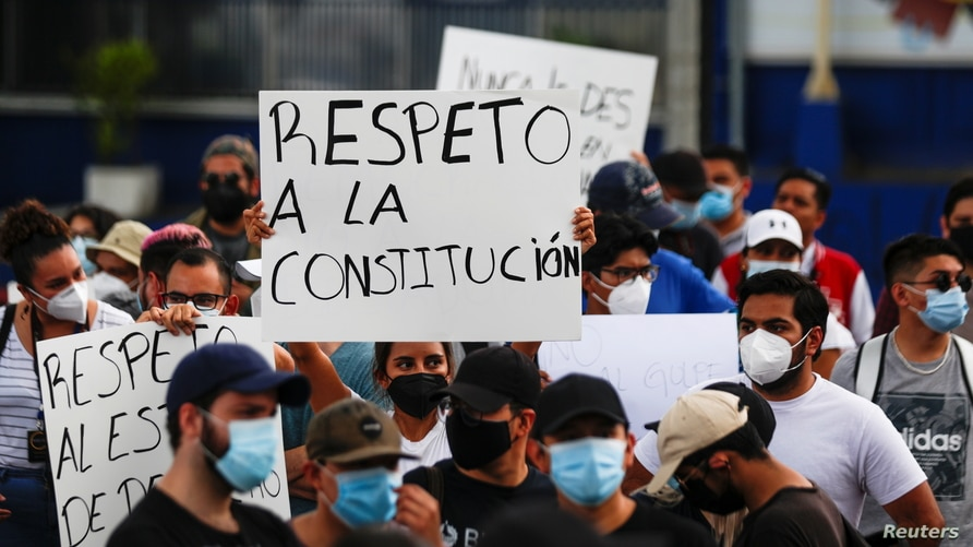 """People hold signs reading """"Respect for the constitution,"""" as they protest against the removal of Supreme Court judges and the Attorney General by El Salvador's congress, in San Salvador, May 2, 2021."""
