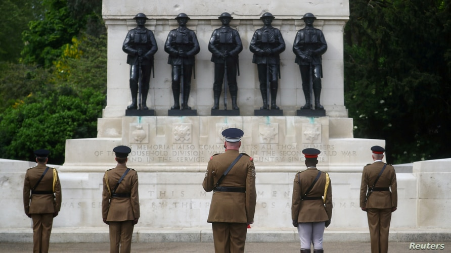 FILE - Senior officers and soldiers of the Household Division stand in front of Guards Memorial in St James's Park during a two minute silence to commemorate the 75th Anniversary of VE Day, London, May 8, 2020.