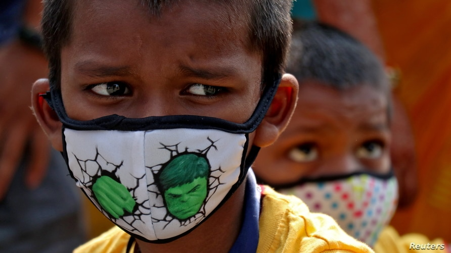 Children wearing protective masks wait to enter the Lokmanya Tilak Terminus railway station, amidst the spread of the COVID-19 in Mumbai, India, April 14, 2021.