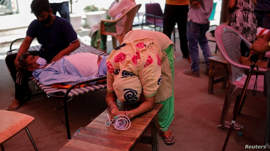 Wife of Nanhe Pal, 52, cries as she pleads for oxygen support for her husband, who is suffering from breathing problem at a Gurudwara (Sikh temple), amidst the spread of COVID-19, in Ghaziabad, India, May 3, 2021.